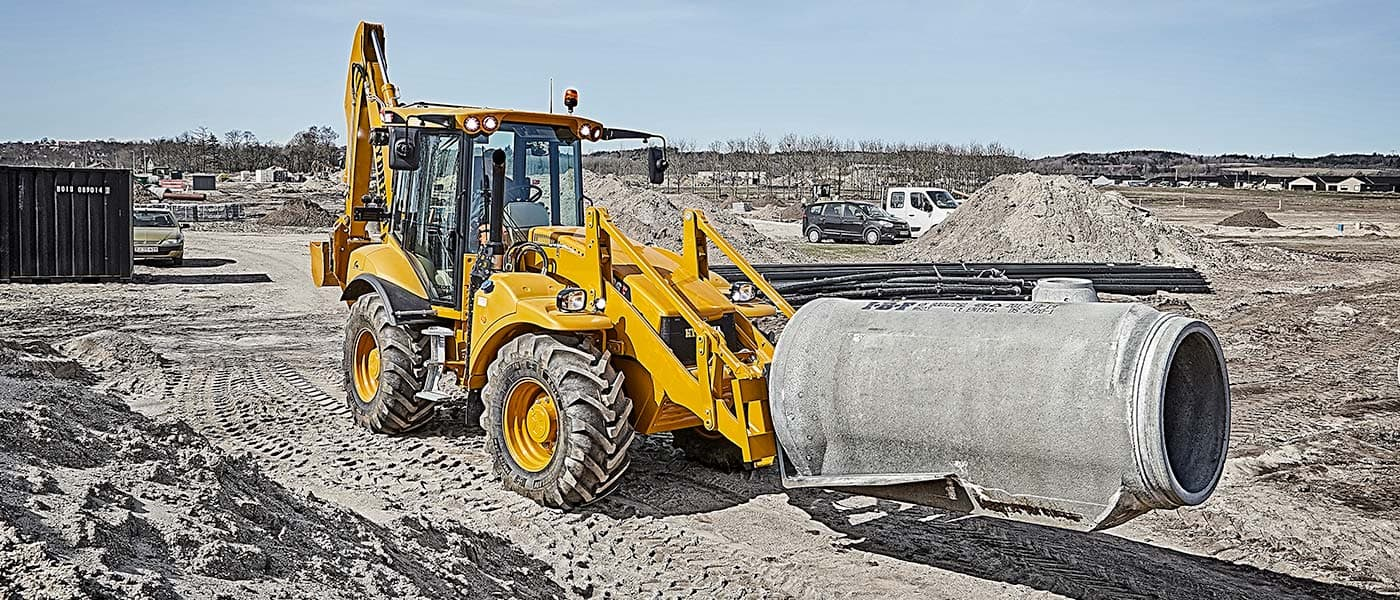 Hydrema 906F backhoe loader transporting a concrete pipe